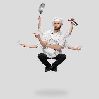 Kocher koch bäcker in uniform multitasking wie shiva isoliert auf grauem studiohintergrund