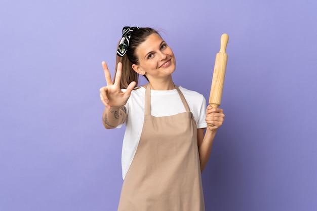 Kocher slowakische frau isoliert auf lila hintergrund glücklich und zählt drei mit den fingern