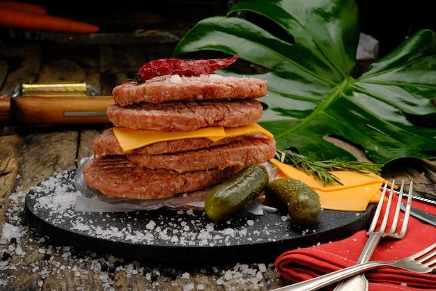 Kochfertige fleischbällchen auf einem schwarzen teller auf einem holztisch mit cheddar-käse, salz und gewürzen