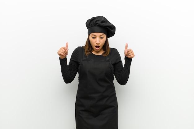 Kochfrau, die sich schockiert, mit offenem mund und erstaunt fühlt, ungläubig und überrascht gegen weiß schaut und nach unten zeigt