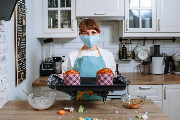 Kochfrau in einer medizinischen maske, die ein backblech mit osterkuchen hält