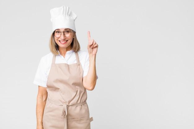 Kochfrau verwirklicht eine idee, die fröhlich finger hebt
