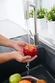 Kochfrau wäscht einen apfel unter fließendem wasser aus einem wasserhahn