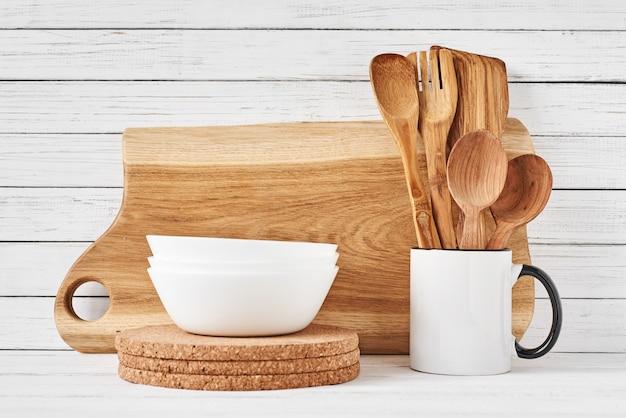 Kochgeräte und schneidebrett auf weißer tabelle