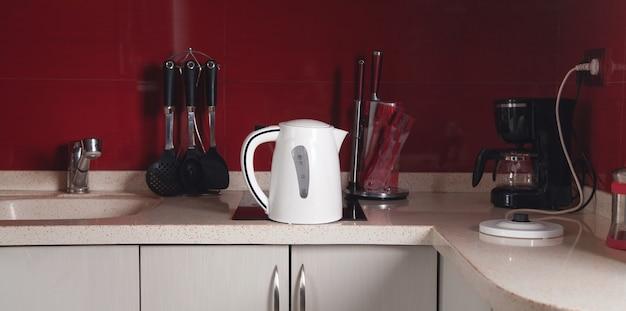 Kochgeschirr, weißer wasserkocher in der küche.