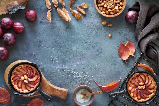 Kochhintergrund mit roten pflaumen, pflaumenkrümelkuchen, erdnüssen, herbstlaub, kopierraum