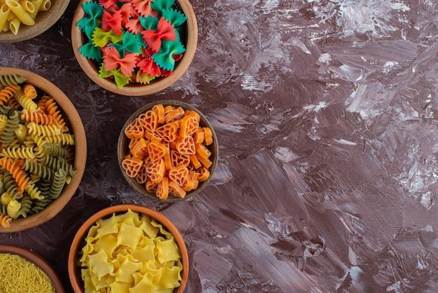 Kochkonzept mit verschiedenen rohen nudeln auf marmoroberfläche.