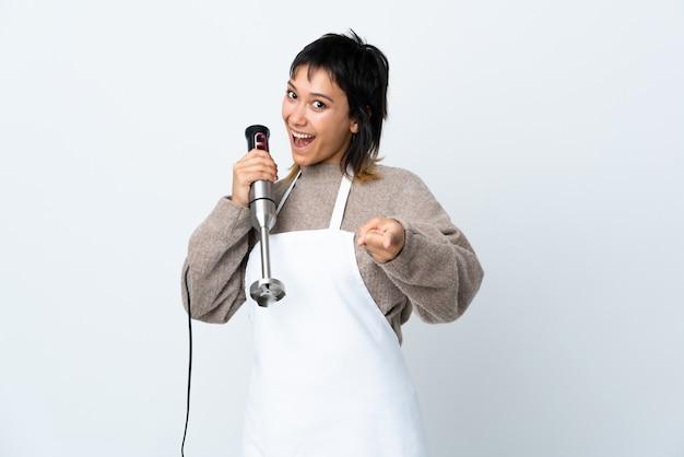 Kochmädchen, das stabmixer über isolierten weißen punktfinger auf sie verwendet