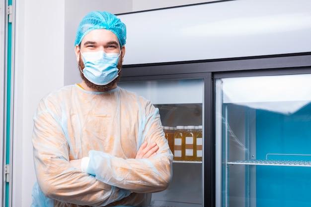 Kochmann in der küche mit verschränkten armen, die gesichtsmaske tragen