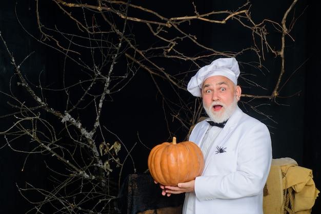 Kochmann mit kürbismannkoch in uniform mit kürbisherbstrezeptkonzept glückliches halloween