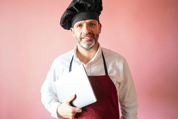 Kochmann mit laptop mit rosa wand