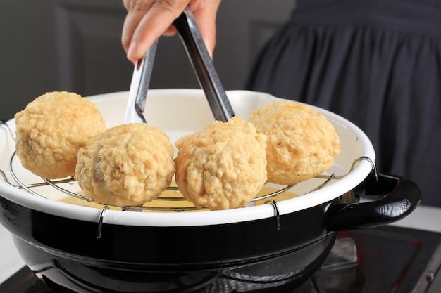 Kochprozess: asiatische weibliche hand hält rostfreie zangen in frittierter pfanne, braten von bakso goreng oder fried chicken oder shrimp meatball