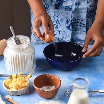 Kochprozess fügen ei und mehl hinzu frauenhand in der küche mit vintage-schürze