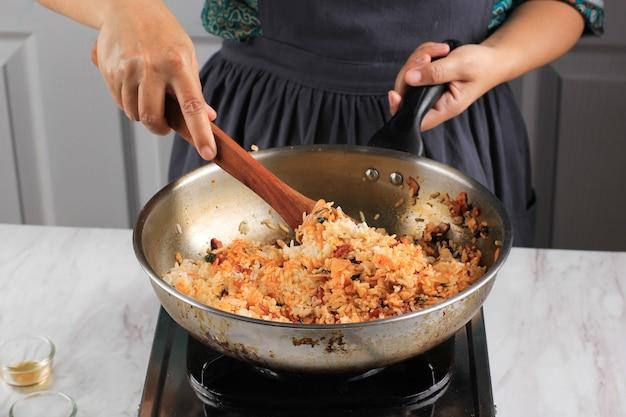 Kochprozess: herstellung von koreanischem kimchi fried rice oder bokkeumbap mit einer rostfreien wok-pfanne, mix stir fry kimchi mit weißem reis (bap).