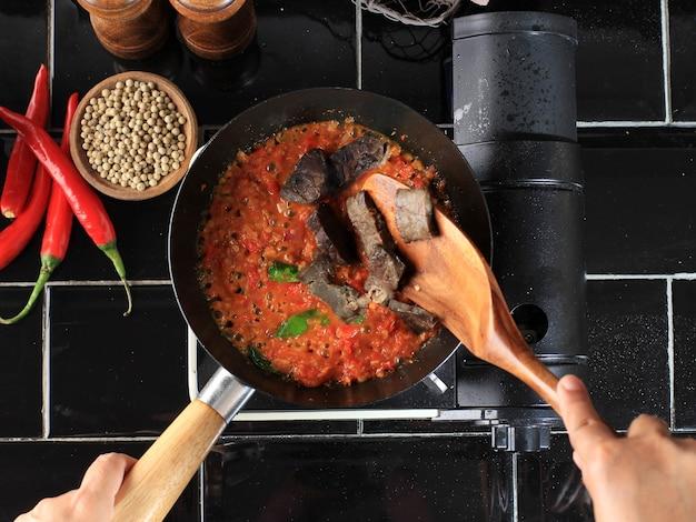 Kochprozess saute sambal oder sambel oder spicy sauce mit limettenblatt auf einer pfanne in der küche