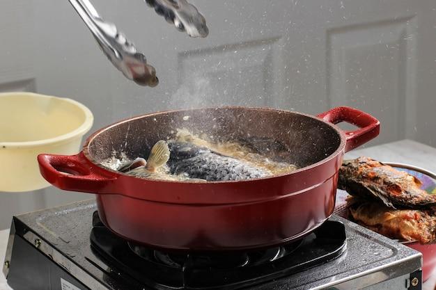 Kochprozess zu hause ölspritzer beim kochen von fisch mit roter pfanne