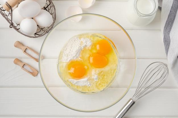 Kochteig für traditionelle dünne pfannkuchen oder crepes. eier, mehl, salz, zucker in einer schüssel auf einem weißen hölzernen hintergrund.