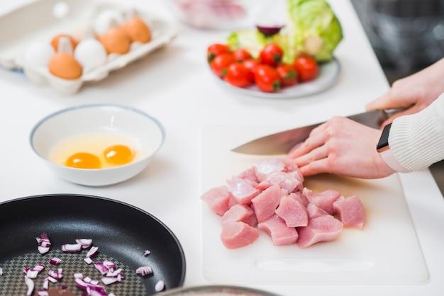 Kochtisch mit den händen, die fleisch schneiden