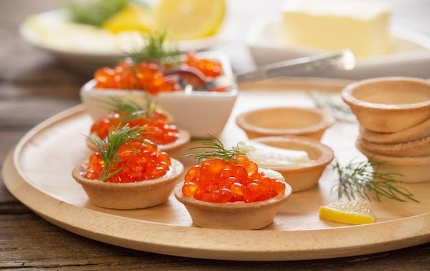 Kochtörtchen mit rotem kaviar auf holztisch