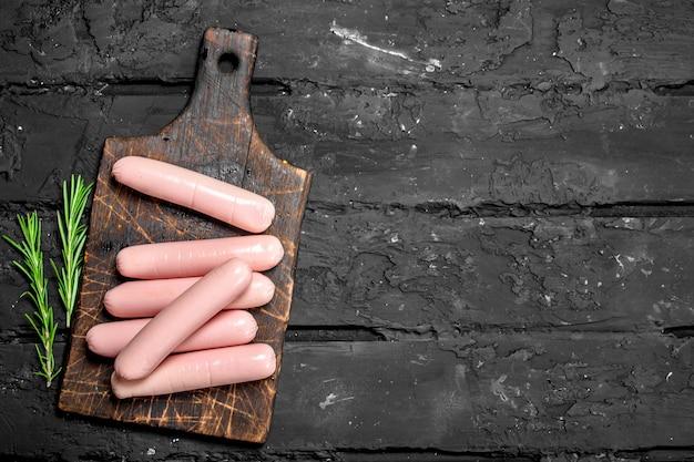 Kochwürste mit rosmarin. auf schwarzem rustikalem hintergrund.