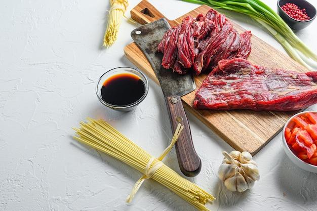 Kochzutaten für die herstellung von gebratenem yakisoba mit rindfleisch. seitenansicht auf weißem tisch mit platz für text.