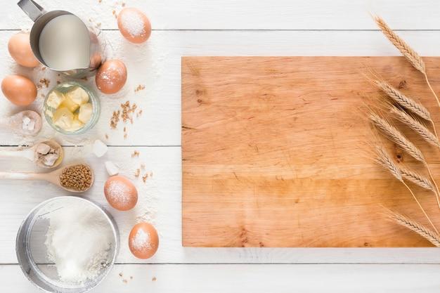 Kochzutaten für hefeteig und gebäck, eier, mehl und milch auf weißem rustikalem holz. draufsicht