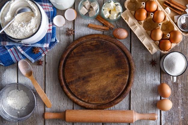 Kochzutaten für teig- und gebäckherstellung und hölzernes pizzabrett auf rustikalem holz. draufsicht