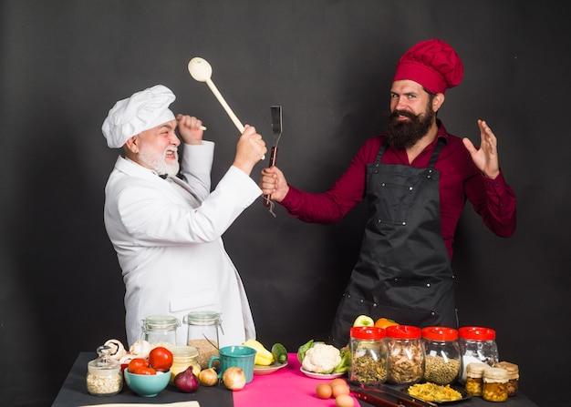 Köche in der küche zwei köche kämpfen in der küche küche kochen bärtiger koch mann leckeres essen männlich