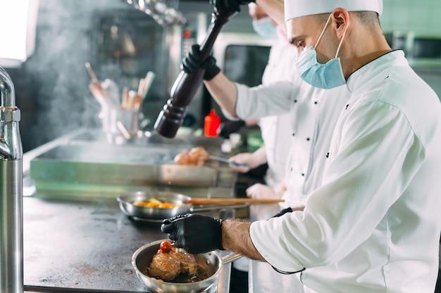 Köche in schutzmasken und handschuhen bereiten speisen in der küche eines restaurants oder hotels zu.