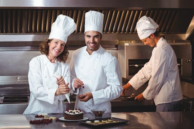 Köche präsentieren den kuchen, den sie gerade gemacht haben