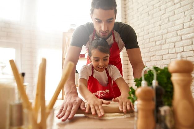 Köche rollen teig auf küche aus.