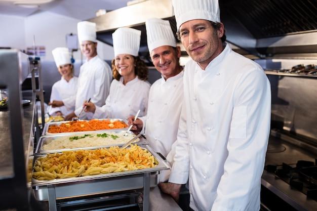 Köche stehen an serviertabletts mit nudeln