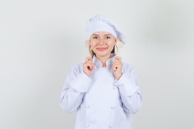 Köchin der frau, die hölzerne löffel hinter den ohren in der weißen uniform hält und fröhlich schaut