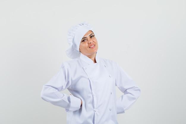 Köchin der hände, die hände auf taille in der weißen uniform hält und fröhlich schaut
