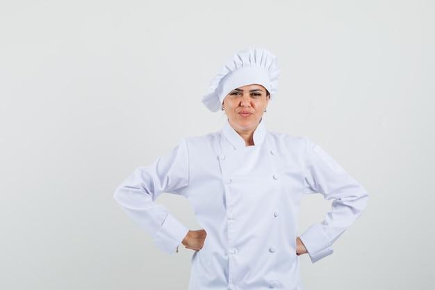 Köchin der hände, die hände auf taille in der weißen uniform hält und zuversichtlich schaut