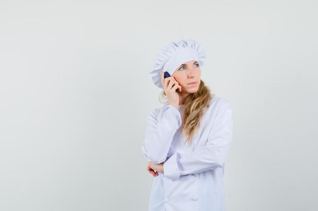 Köchin, die auf handy in weißer uniform spricht und nachdenklich schaut