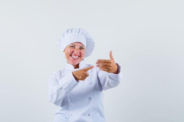 Köchin, die auf liste in weißer uniform zeigt und lustig schaut