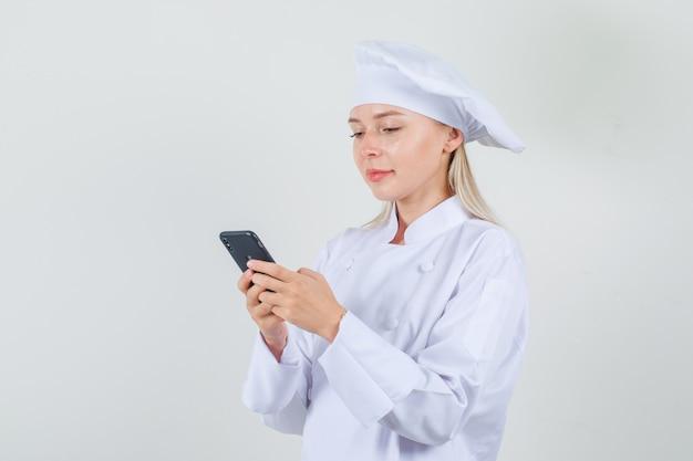Köchin, die auf smartphone tippt und in der weißen uniform lächelt
