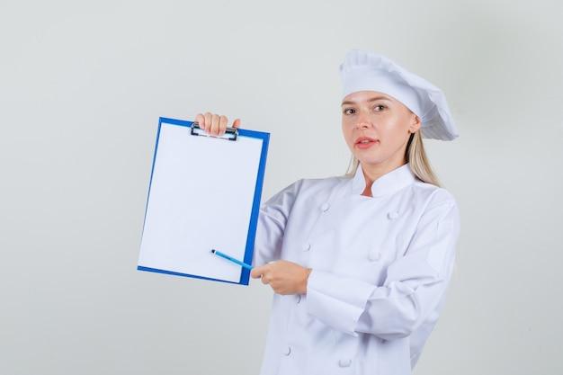 Köchin, die bleistift auf zwischenablage in weißer uniform zeigt