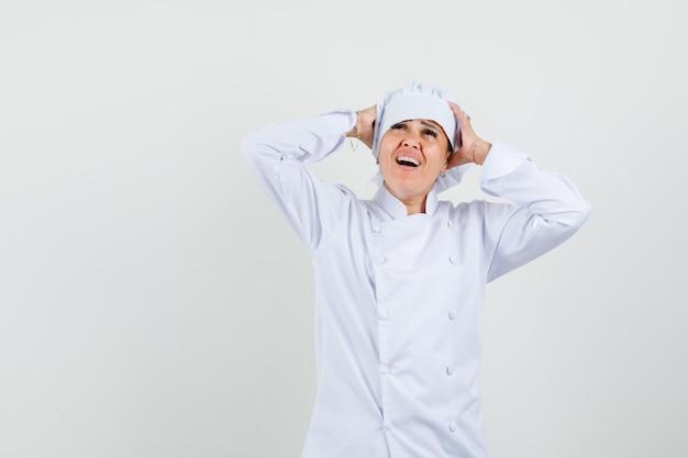Köchin, die den kopf in den händen in der weißen uniform umklammert und glücklich schaut