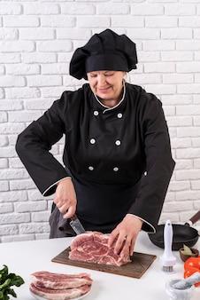 Köchin, die fleisch schneidet