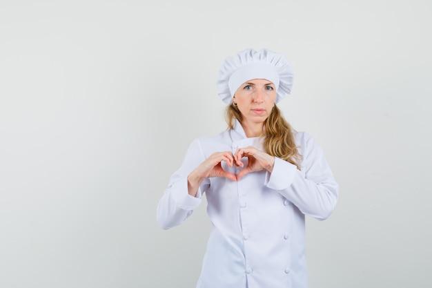 Köchin, die herzgeste in der weißen uniform zeigt und positiv schaut