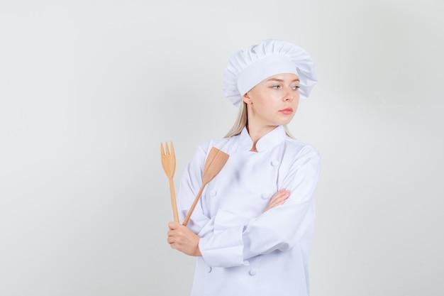 Köchin, die hölzerne gabel und spatel in der weißen uniform hält und ernst schaut.