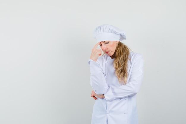 Köchin, die in der denkenden haltung in der weißen uniform steht und traurig schaut