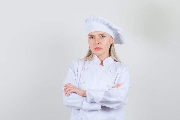 Köchin, die kamera mit verschränkten armen in der weißen uniform betrachtet und ernst schaut. vorderansicht.