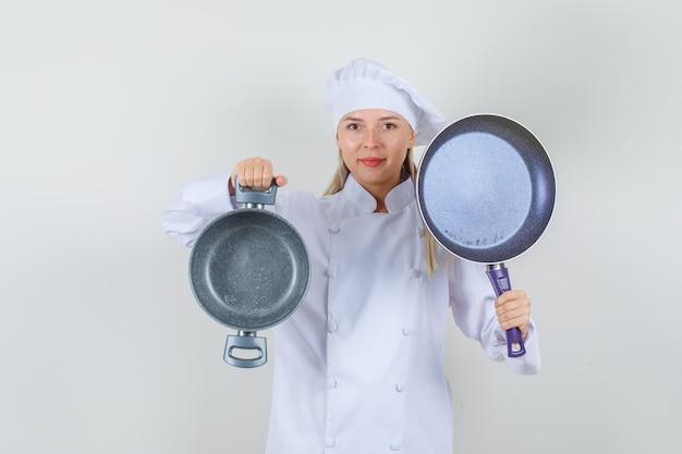Köchin, die leere pfannen hält und in der weißen uniform lächelt