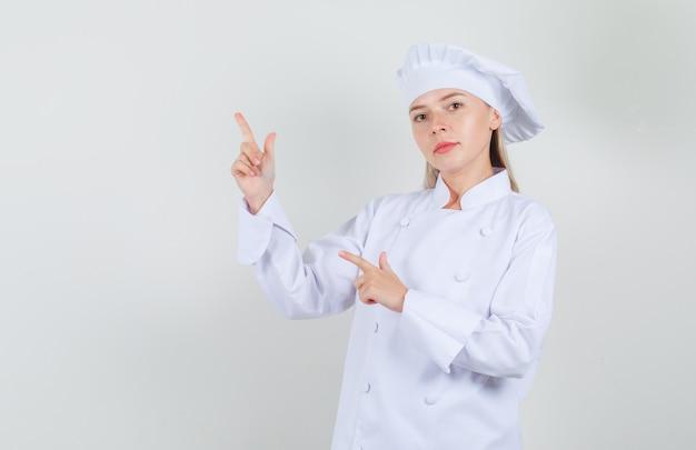 Köchin, die mit waffengeste in weißer uniform zur seite zeigt