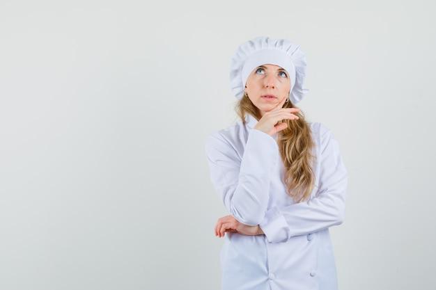 Köchin, die nach oben schaut, während kinn auf hand in weißer uniform stützt und nachdenklich schaut.