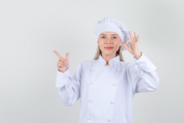 Köchin, die ok zeichen und waffengeste in der weißen uniform zeigt und fröhlich aussieht.