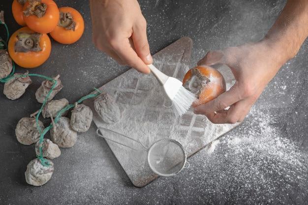 Köchin, die persimone mit mehl auf schwarzer oberfläche verziert